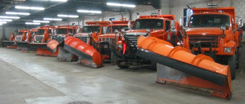 Trucks have their snow plows mounted and wait for the next storm